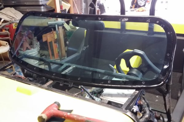 To screw the Lexan to the windshield frame, Dale had to cut it from the car and devise a method to fasten it back. He then drilled and tapped the frame and secured the Lexan to the frame with counter-sunk screws.