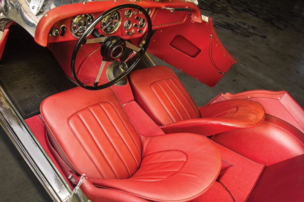 The interior has original Triumph seat bases, but upholstered with fresh red leather.
