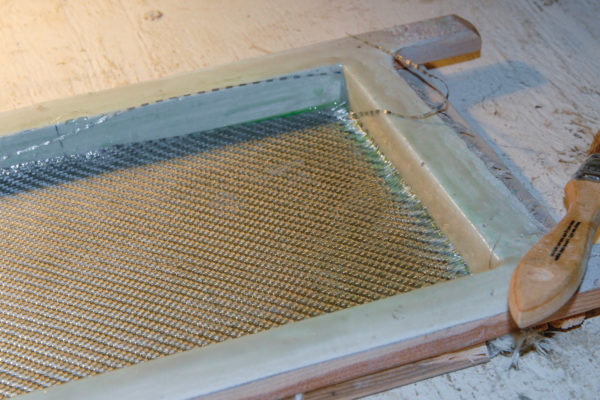 Back up your initial layer of Barracuda glass with six more layers, alternating between conventional fiberglass cloth and fiberglass mat. Place the mold under the heat lamps to cure the part.