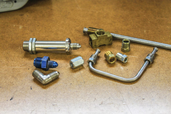 No doubt the hardest part of building a brake system is finding the right brake line fittings. It can be frustrating, too, since there can be several kinds and sizes of fittings in the system, metric and SAE and even AN-style fittings. The four fittings to the left are AN fittings including a through-frame fitting, SAE-AN adapters (blue and 90-degree) and a tube nut. AN fittings have a 37-degree flare as compared to 45-degree flares on SAE units. Items on the right include 3/16- and 1/4-inch flare fittings and a T-fitting.