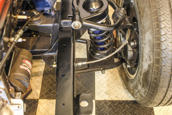 On this disc brake setup from a Mustang II front end, the builder used a through-frame fitting for the flexible stainless steel braided brake line.