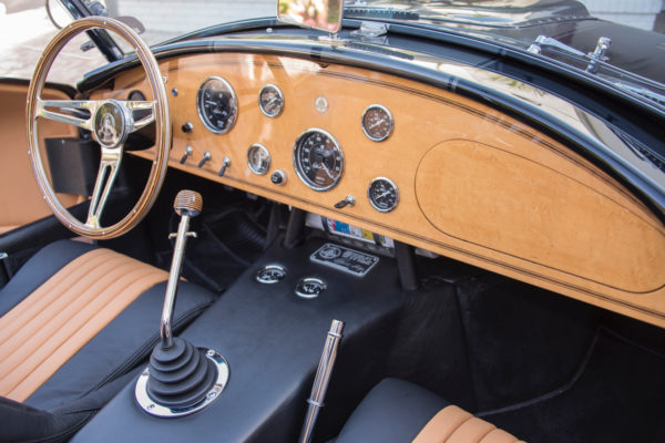 Birdseye maple was handcrafted by a woodworker to form the dash, steering wheel and gearshift knob.