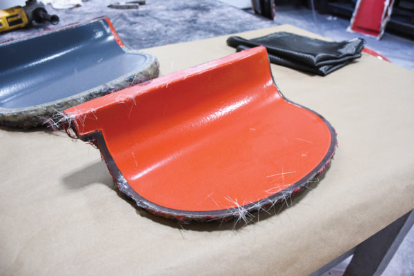 This mold for a gauge-face pod is coated with an orange tooling gelcoat. Nate Johnson says that before layup, it should have a perfectly smooth surface. It's coated with a high-temp, mold-release carnauba wax buffed to a smooth finish, followed by a layer of clear gelcoat that will serve as a UV-protector on the completed part.