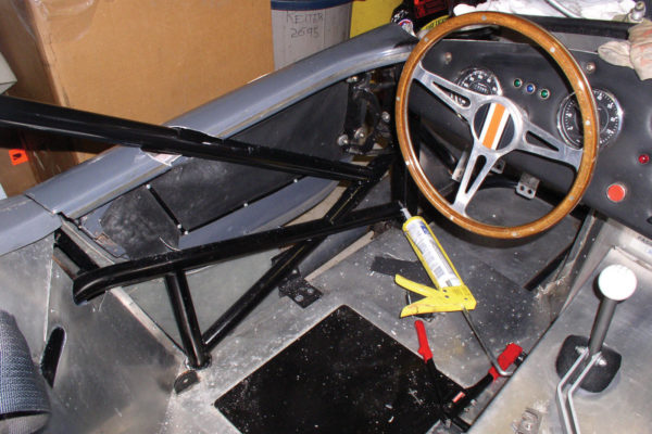"The driver's side of the car with the side cage installed. The lower ""X"" ties together from two bulkhead crossmembers of the Factory Five frame, and also ties in the longitudinal chassis crossmember via the vertical tube. Part of the design was to fit between the seat and the 