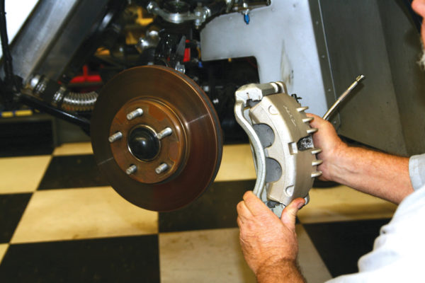 After disconnecting the brake fluid hose and capping off the end, break loose the caliper mounting bolts from the back side of the rotor. Then lift off the caliper, keeping the brake line hose vertical to avoid any fluid spills.