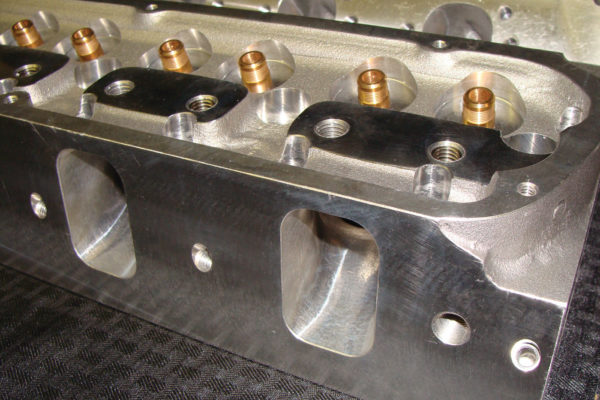 The pushrod slots, located next to the threaded holes for the rocker assembly, are slightly offset to clear the ports.