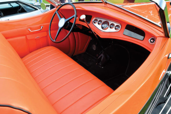 The striking orange leather interior has a few intriguing details upon  thorough inspection. The Rolls-Royce steering wheel features a machined Ford piston as the horn button. There is a glove compartment door on the right, but the matching door on the left hides the heating and air conditioning controls. The tall Lokar shifter actuates the TH400 transmission.