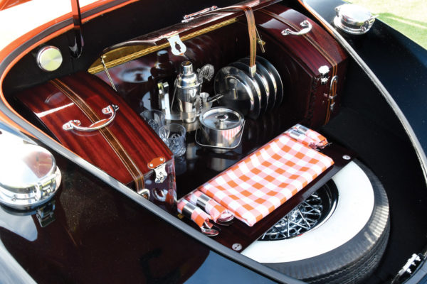 The custom-made luggage in the trunk holds all the fixings for a picnic, along with a surprise. 