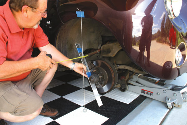 Here we are measuring backspacing, using a custom-made tool. Whatever tool you come up with has to be able to give you two measurements at the same time — the distance from the hub face that the wheel bolts to (backspace) and the distance from the centerline of the axle (radial). You can see our version in this photo — a good solid straight edge and two measuring devices. Be sure that the ruler taking the radial distance is always zeroed on the axle centerline.