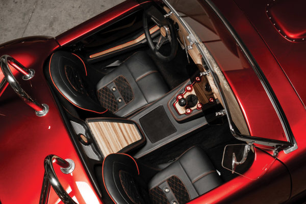 Custom speaker housings with a zebrawood medallion are mounted in the waterfall between the seats. The entire stereo system is hidden and operates via Bluetooth connection.