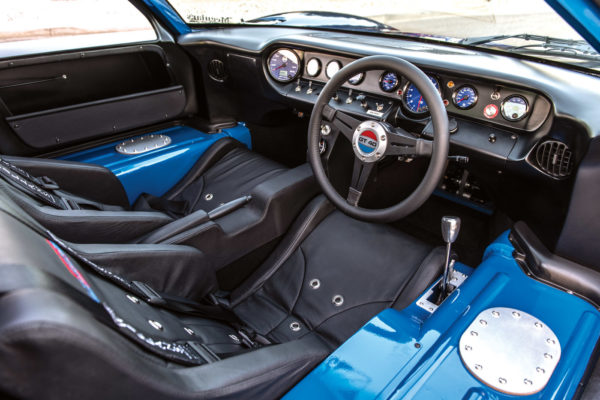 The snug, right-hand drive cockpit is dressed with custom Stitchcraft upholstery, layered with Dynamat and DEI heat insulation. Engine vitals are monitored by custom Speedhut gauges.