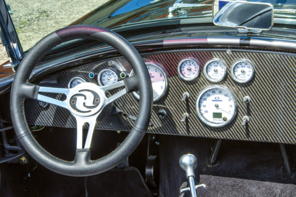A contemporary cockpit treatment includes a carbon fiber overlay and a fatter steering rim for track duty. A traditional wooden rim is optional.