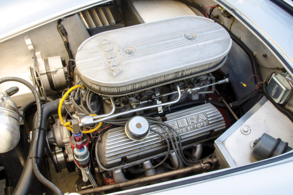 The 300 hp Ford 302 ci engine is slightly larger than the original 289 slab side's, with dual 600 cfm Holley carbs.