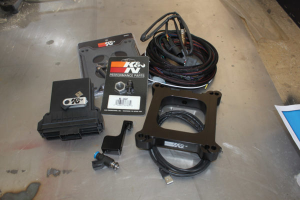 Here are the components of the K&N electronic carburetor injection system (clockwise from left): electronic control unit with USB drive containing necessary software, gaskets and carburetor studs, O2 sensor bung and NPT fitting, O2 sensor and wiring harness, ECI plate and USB cable, injector and fuel rail.
