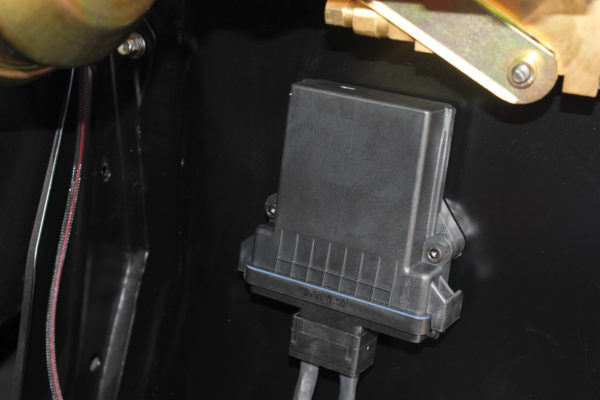 Find a suitable location to mount the ECU  box that's away from direct heat, wet conditions and any mechanical interference. We decided  to mount it on an inner fender surface on  the driver's side to facilitate wiring for our installation. Two bolts through drilled holes securely mounts the unit.