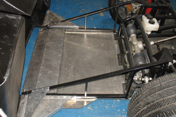 The fiberglass nose of the car is attached to the front subframe with pivots and pins, and an aluminum-panel splitter is riveted underneath.