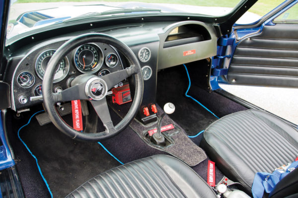 Doug Hanner installed aircraft switches for controlling the radiator fan and fuel pump. The production Corvette dash was changed to a Grand Sport-style in fiberglass with no glove box or vinyl coverings, and Stewart Warner fuel and oil temp gauges were added to the center console.