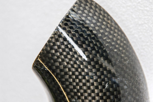 This carbon fiber exhaust shield has a scratch in the surface (intentionally damaged to illustrate the repair process).