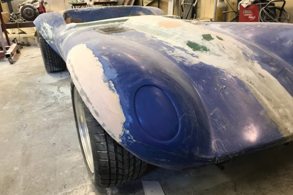 To make the front fender flares, John first applied masking tape to create the line for cutting the fender. He then partially sliced it with a 5-inch cutoff wheel, leaving the cut piece attached at the front and rear. After spraying glue onto the piece, he attached poster board and trimmed it with a razor blade to the shape of the cut piece. He then removed the poster board and attached it to the fender on the other side in order to keep the shapes the same. Once the fenders were cut, he spread them out by inserting a 1-inch piece of foam, and he applied fiberglass matte and body filler for the final shaping.