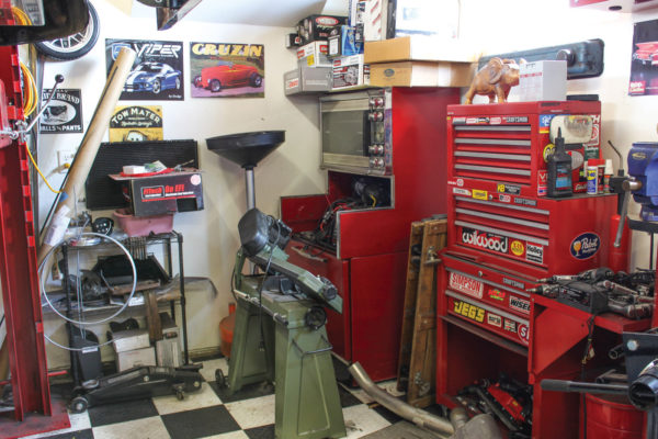 This crowded corner of the Taj Garage holds my castoff, repurposed double oven used for powder-coating, plus a horizontal band saw, oil drain, and metric tool rollaway.