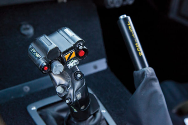Military-grade details are evident throughout, such as an actual helicopter cyclic stick serving as a gearshift lever.