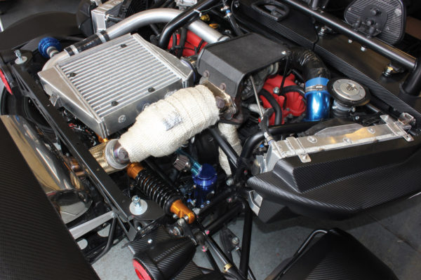 The Subaru flat-four sits inline with its intercooler on top and oil cooler on the side.