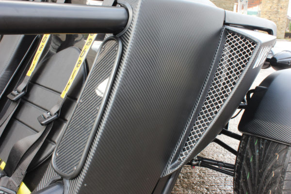Carbon fiber air scoops on the sides direct air through to the midmounted, inline Subaru flat-four.